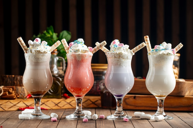 Вид сбоку на различные сладкие молочные коктейли на деревянном фоне
