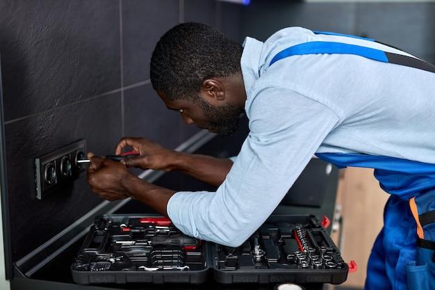 ドライバーツールを使用して、住宅用電気システムのソケットを修理する電気技師の側面図。仕事中に青いオーバーオールで熟練した自信のあるアフリカの便利屋、集中して集中
