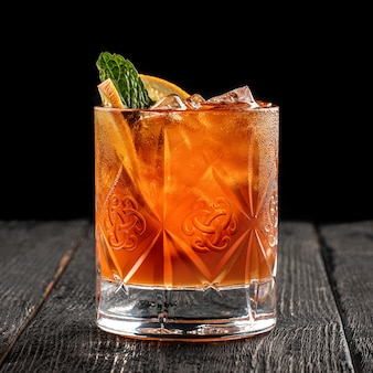 Вид сбоку на свежий алкогольный коктейль, украшенный апельсином