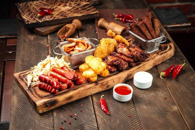 Вид сбоку на жареные соленые пивные закуски на деревянной доске с соусами