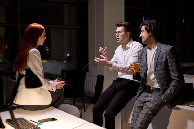 Вид сбоку на дружелюбных офисных работников, коллег, разговаривающих после тяжелого рабочего дня, ночью. рыжая женщина и двое парней в официальной одежде обсуждают, делают перерыв, деловая команда в зале заседаний