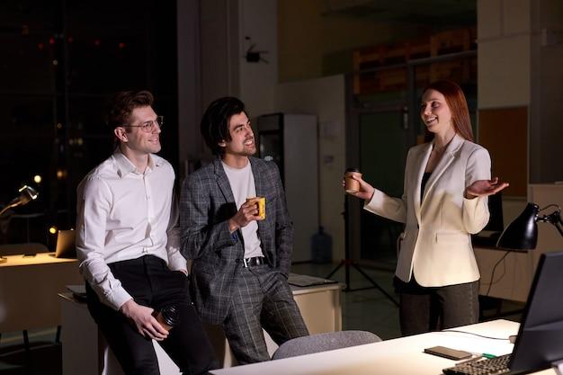 친절한 사무실 직원, 밤에 열심히 일한 후 이야기를 나누는 동료에 대한 측면 보기. 빨간 머리 여자와 정장 차림의 두 남자, 토론, 휴식, 회의실에서 비즈니스 팀