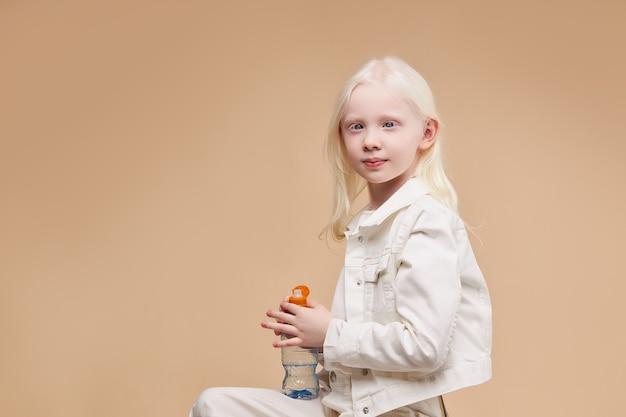 Вид сбоку на великолепного спокойного и застенчивого ребенка-альбиноса, сидящего с изолированной бутылкой с водой