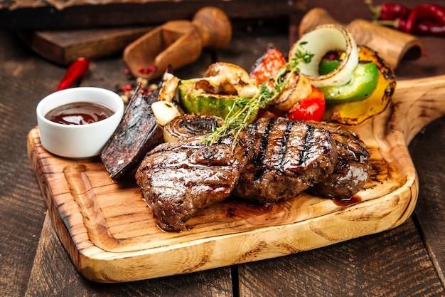 Вид сбоку на стейки из говядины на гриле с овощами и соусом на деревянной доске