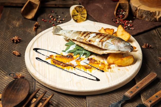 Вид сбоку на рыбу-гриль с картофелем, подаваемую на деревянной доске