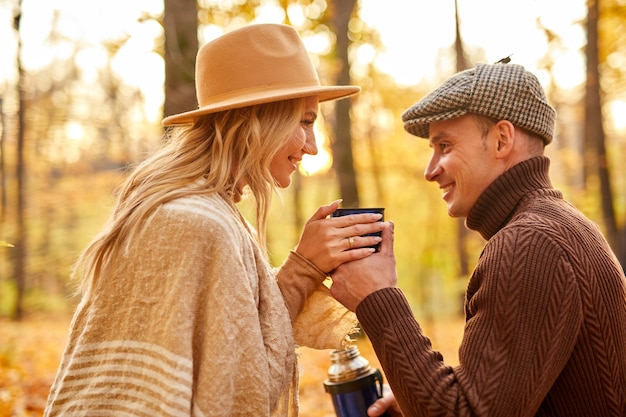 가 숲에서 뜨거운 차를 마시는 행복 한 커플에 측면보기