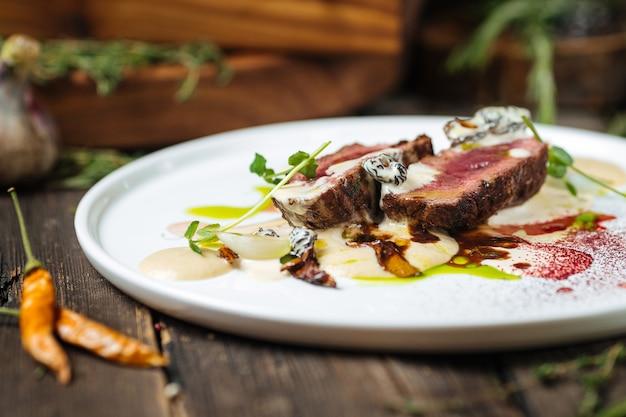 Вид сбоку на итальянский бефстроганов с картофельным пюре с грибами на плоской белой тарелке на темном деревянном столе