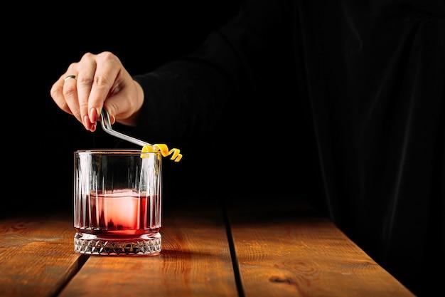 Вид сбоку на приготовление коктейля негрони в старомодном стекле на деревянном столе