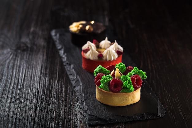 검은 슬레이트 배경에 신선한 과일, 초콜릿, 견과류, 크림이 있는 미니 파티 타르트의 측면 전망. 달콤한 케이크