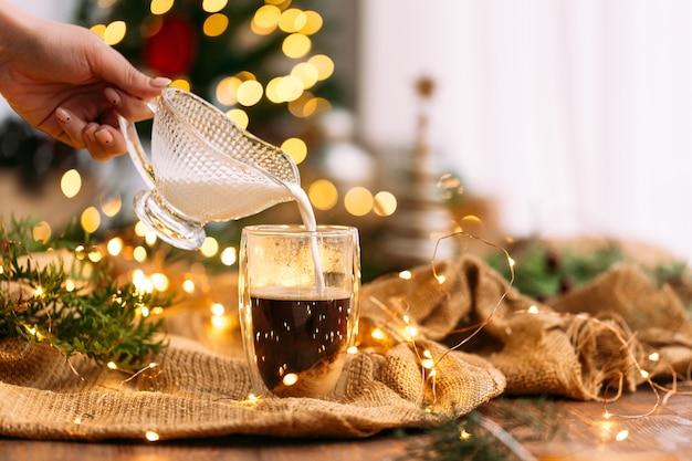 Вид сбоку на наливание молока в стеклянную кружку кофе на фоне праздничной гирлянды