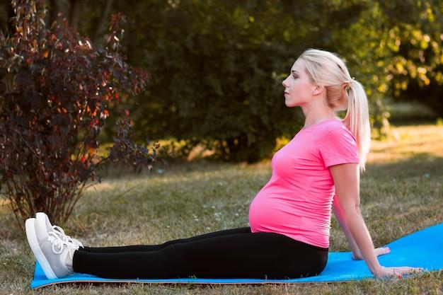 Вид сбоку на беременную женщину, сидящую на каремате на природе