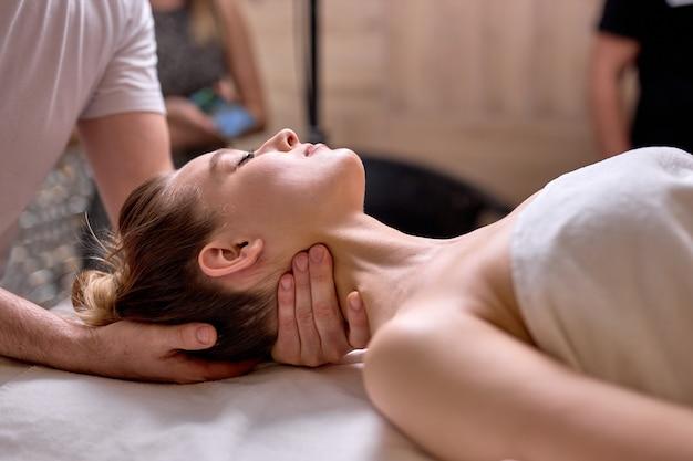 背中に横たわっている女性のクライアントに首と肩の健康的なマッサージをしているプロのクロップドセラピストの側面図、側面図。スパサロンにて