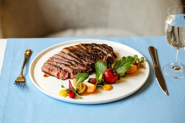 青いテーブルの上に新鮮な野菜のサラダとスライスしたリブアイビーフステーキの側面図