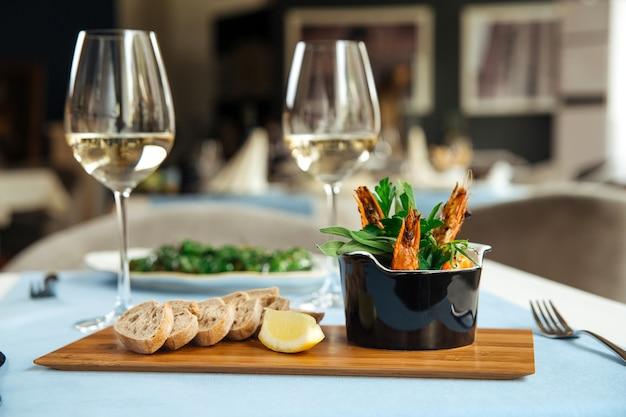 Вид сбоку на испанское блюдо гамбас пиль-пили креветки на столе в ресторане
