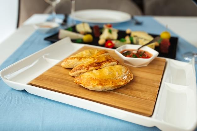 レストランのテーブルにソースとスペインのパイエンパナーダの側面図