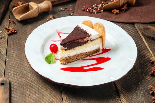 木製のテーブルにベリーソースをかけたティラミスケーキの側面図