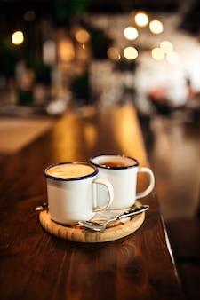 Вид сбоку на две кружки утреннего кофе на столе в кафе