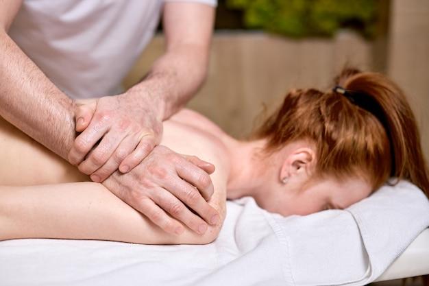 腹の上に横たわる背中と肩のマッサージを楽しんでいる認識できない赤毛の女性の側面図