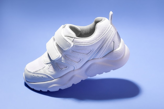 Side view one flying white child sneaker with velcro fasteners simulating a walk isolated on a purpl...