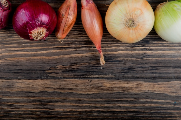 Side view of onions as red white shallot and sweet on wooden background with copy space