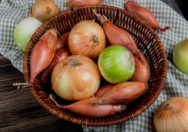 Side view of onions as shallot sweet and white ones in basket on plaid cloth and wooden background