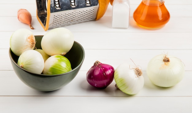 Side view of onions in bowl with other ones butter salt grater on wooden background
