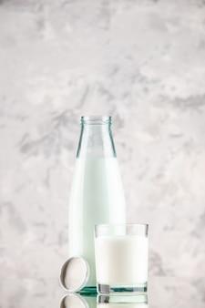 Vista laterale della bottiglia di vetro aperta e della tazza piena di tappo per il latte