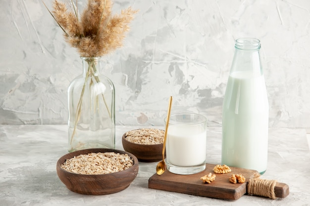 Side view of open glass bottle cup filled with milk spoon and walnut oats in brown pot on ice wall