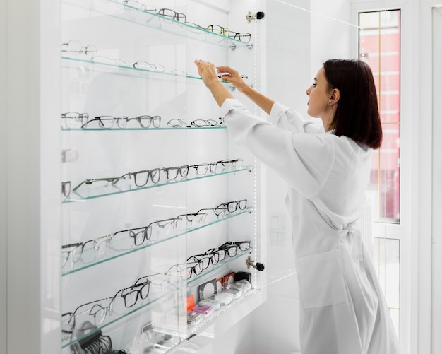Side view of optician with glasses display