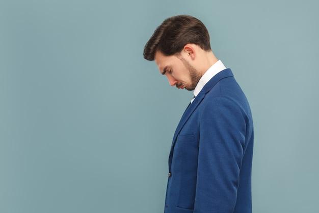 青いスーツと白いシャツを着た悲しい、不幸な泣いているハンサムなひげを生やしたビジネスマンの側面図または縦断ビュー。水色の背景に分離された屋内スタジオショット
