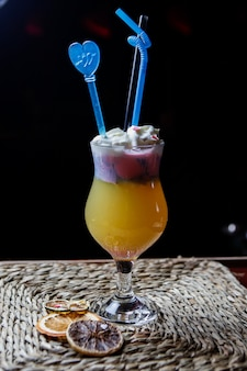 Side view orange creamsicle smoothie with tubules for beverages and dried lemon in serving napkins