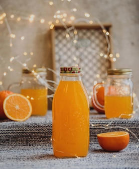 Side view of orange juice in a glass bottle on the table