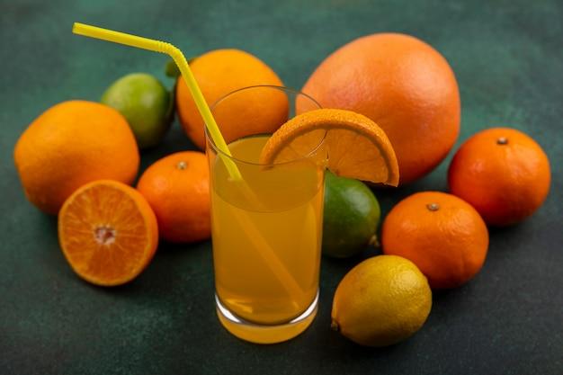 Vista laterale del succo d'arancia in un bicchiere con arance limone lime e pompelmo su uno sfondo verde