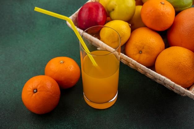 Vista laterale del succo d'arancia in un bicchiere con arance, limoni e prugne in un cesto su uno sfondo verde