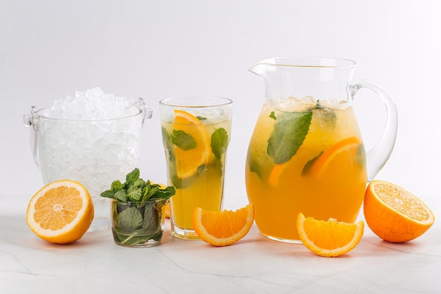 Side view on orange and mint lemonade in a jug and glass on the white background