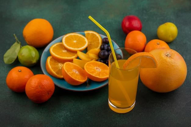 Вид сбоку дольки апельсина со сливой на синей тарелке с апельсиновым соком, грейпфрутом и лимоном с лаймом на зеленом фоне