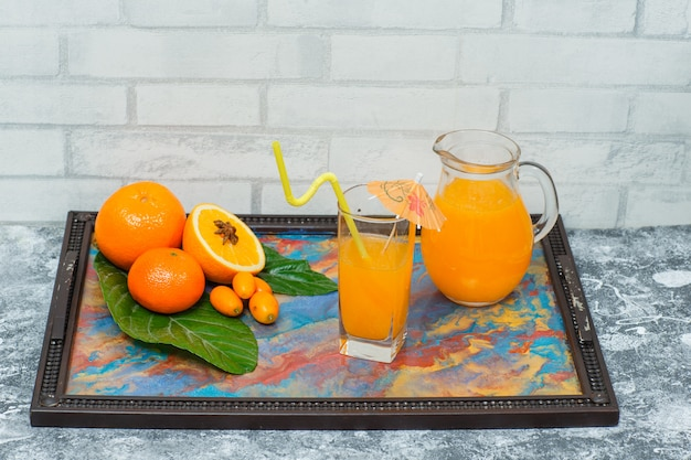 Side view oranges in frame with abstract colors with juice in glasses, leaves, mandarin orange on light brick textured surface. horizontal