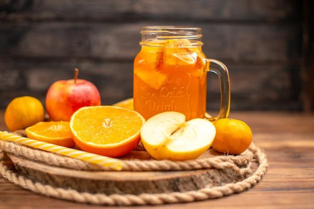 Vista laterale del succo fresco biologico in una bottiglia servita con tubo e frutta su un tagliere e su un tavolo di legno marrone