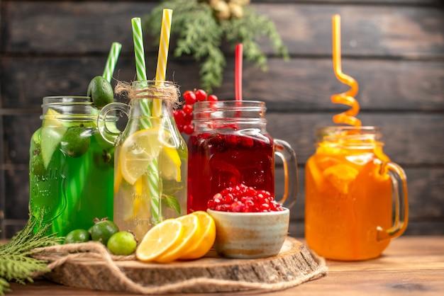 Vista laterale di succhi di frutta freschi biologici in bottiglie serviti con tubi e frutta su un tagliere di legno