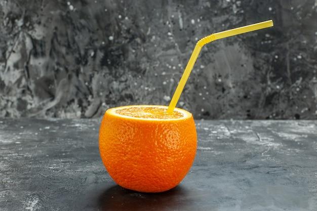 Vista laterale dell'arancia fresca naturale organica tagliata con tubo su sfondo grigio
