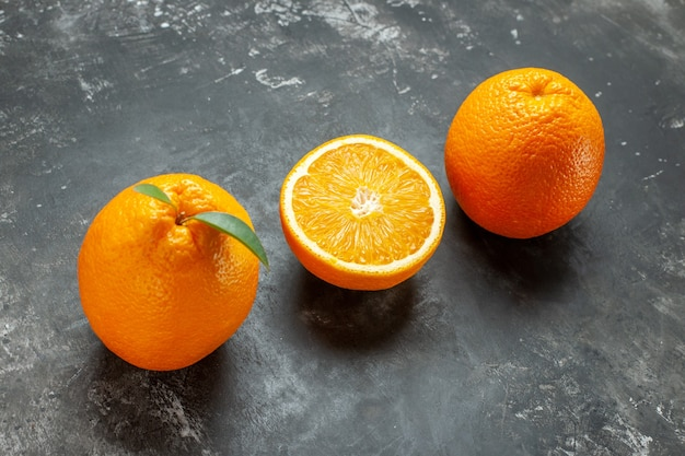 Side view of organic natural whole and cut fresh oranges with leaves on gray background