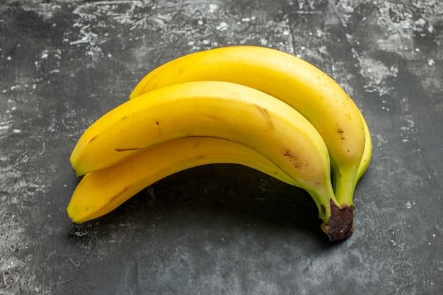 Vista laterale del pacco di banane fresche di fonte di nutrizione organica su sfondo scuro