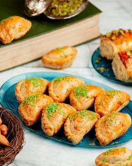 Side view of oriental pastry with nuts and pistachio on platter