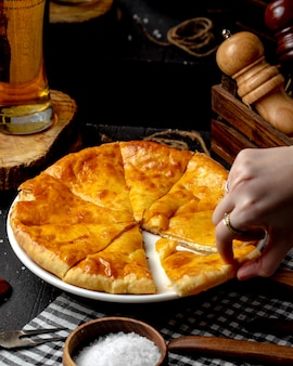 Side view of ossetian pie with cheese on the table