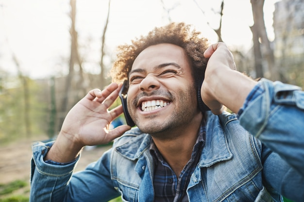 Side-view outdoor portrait of excited happy african man with afro hairstyle holding headphones while listening to music and smiling broadly, being amazed with what he hears.