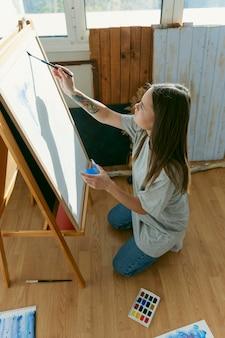 Pittore di vista laterale che disegna un ritratto