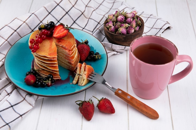 Side view pancakes with black and red currants strawberries with a fork on a plate with a cup of tea on a white checkered towel