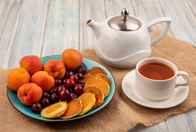 Side view of pancakes with cherries and apricots in plate and cup of tea with teapot on sackcloth and wooden background