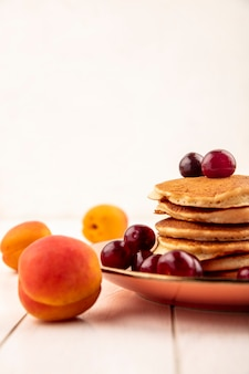 Side view of pancakes with cherries in plate and apricot on wooden surface and white background