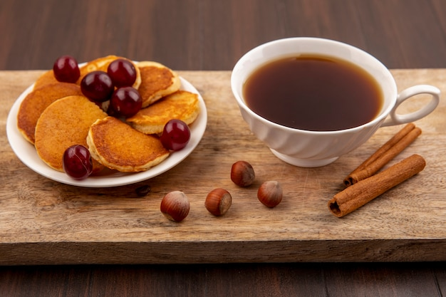 Side view of pancakes with cherries in plate and cup of tea with cinnamon and nuts on cutting board on wooden background